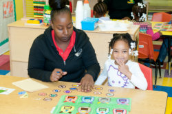 child doing an activity with her teacher